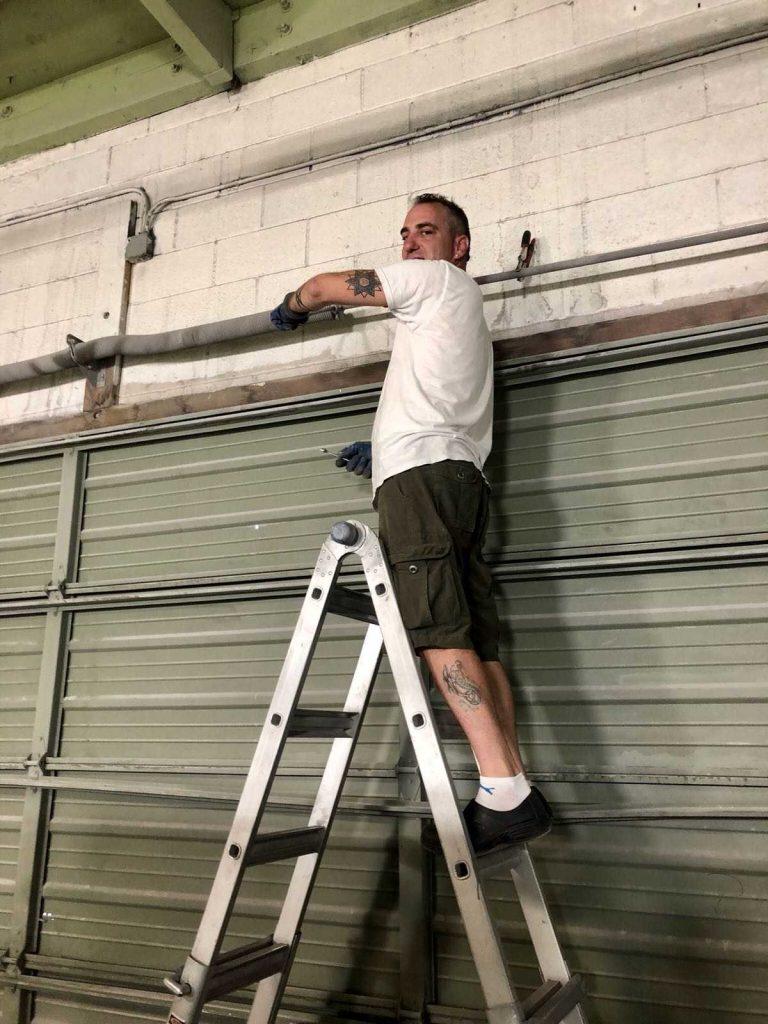 Technician replacing garage door torsion spring