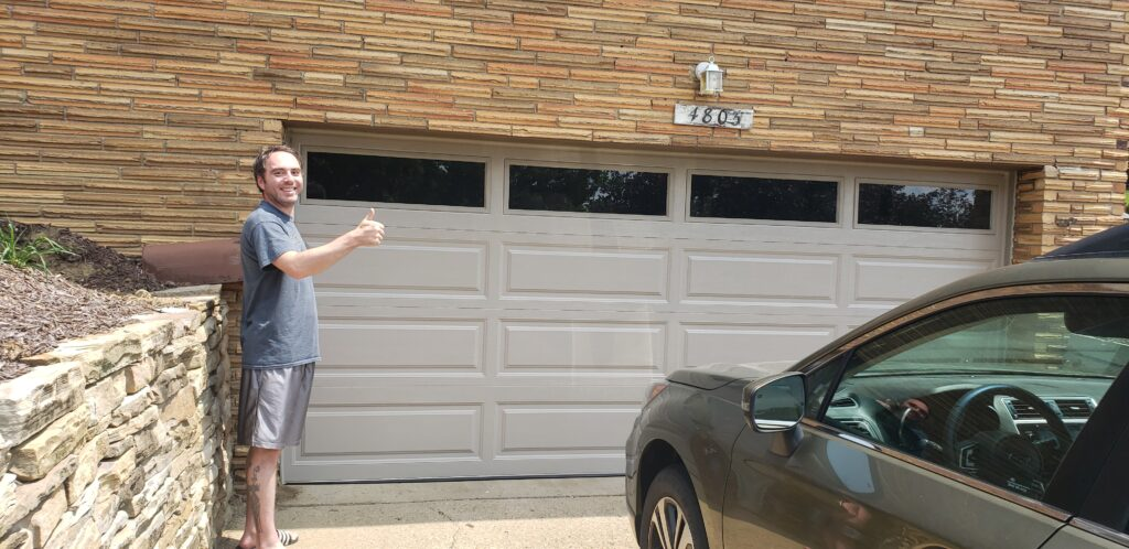 new garage door with happy client thumbs up
